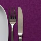 Besteck und Teller auf lila Tischdecke