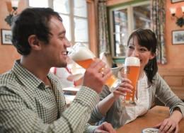 Weltgenusserbe Bayern Mann und Frau stoßen mit Bier an
