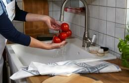 Frau wäscht Tomaten