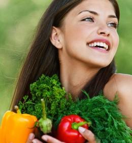 Lachende Frau mit Gemüse im Arm
