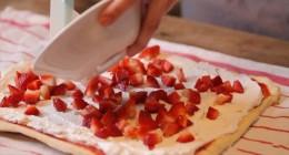 Die Erdbeeren gleichmäßig auf dem Teig verteilen