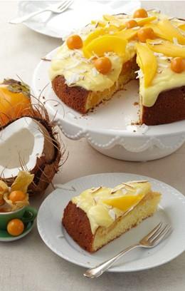 Ein exotischer Mango-Physalis-Kuchen auf einer weißen Tortenplatte.