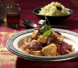 Intensiv gewürztes Chicken Tikka Masala auf einem großen Teller