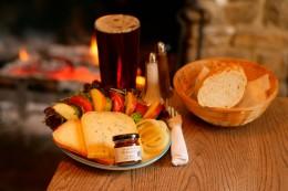 Zu einem Ploughman's Lunch gehören Käse, Brot, Gemüse, Chutney und ein frisches Bier