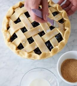 Teigstreifen auf der Füllung einpinseln für Blueberry Pie