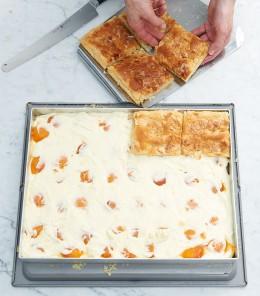 Pudding-Füllung und Aprikosen auf Kuchenboden für Bienenstich verteilen