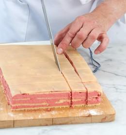 Kuchen mit scharfen Messer in Würfel schneiden für Prinzessinnen-Petits-Fours