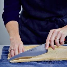 Biskuit auf Küchentuch mit Messer zuschneiden für Bûche de Noël