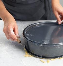 Teig von Springformrand mit Messer entfernen für Gedeckter Apfelkuchen