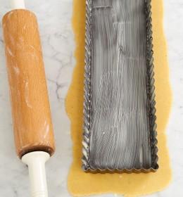 Tarteform auf ausgerolltem Teig mit Rollholz für Tarte au citron