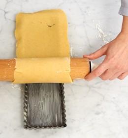 Aufgerollter Teig auf Rollholz über der Tarteform für Tarte au citron