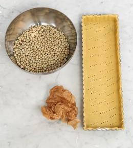 Teig in Tarteform mit Hülsenfrüchten in Schüssel und zerknülltem Backpapier für Tarte au citron