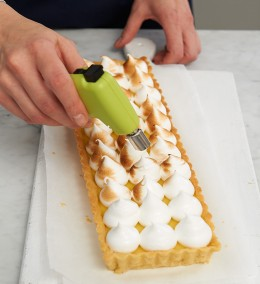 Baisertupfen mit Crème-brûlée-Brenner abflämmen für Tarte au citron