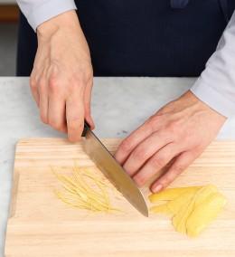 Zitronenschale mit Messer fein schneiden für Garnitur der Tarte au citron