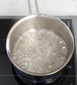 Zuckerwasser in Topf aufkochen für garnitur der Tarte au citron