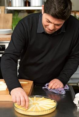 Tim Mälzer breitet eine Spargel-Polenta-Tarte zu.