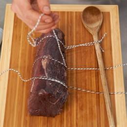 Filet mit Küchengarn umwickeln und am Kochlöffel befestigen