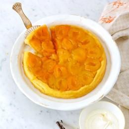 Orange-gelbe Aprikosen-Tarte-Tatin auf weißem Kuchenteller mit Sahne