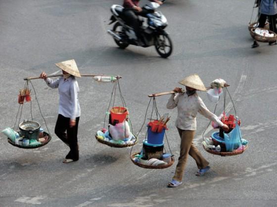 Vietnamesische Straßenköchinnen brauchen keine aufwendige Ausstattung, nur eine Tragestange mit zwei Körben für die Zutaten und ein paar einfache Utensilien, um banh-khoai-Pfannkuchen und andere Köst