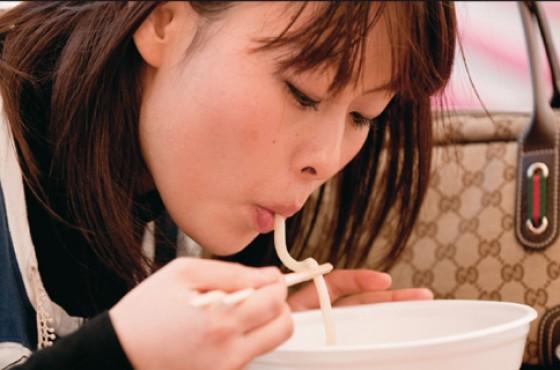 Junge Frau die Sobanudeln isst