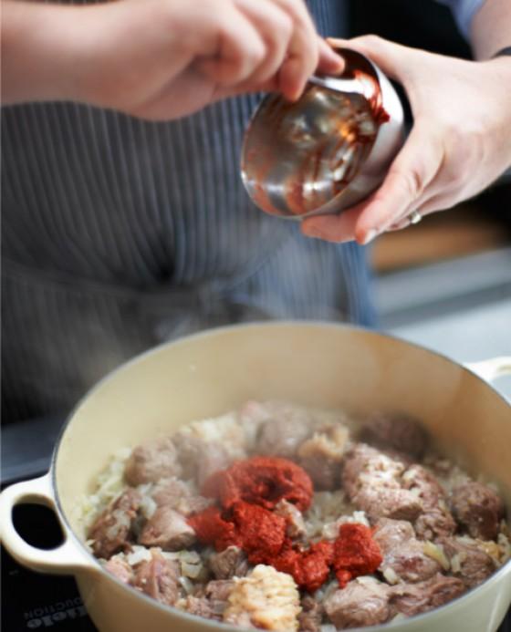 Paprikawürze zum Gulaschfleisch geben