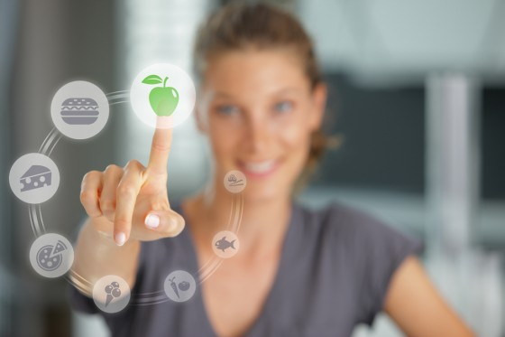 Frau wählt am Touch Screen Essen
