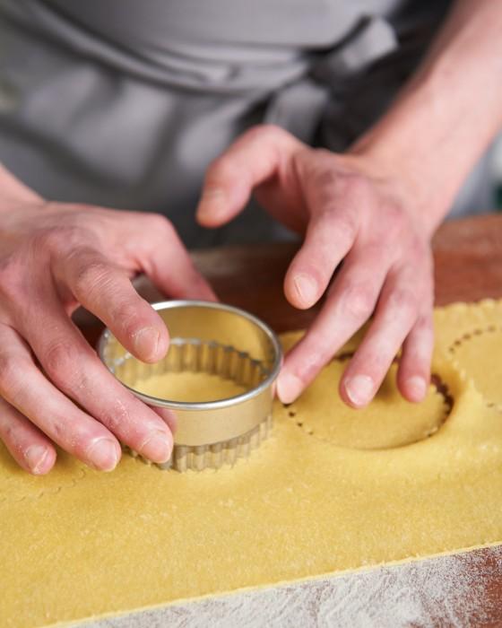 Mit einer Form Kreise asu dem Pastateig ausstechen