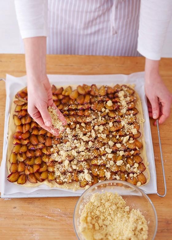 Streusel-auf-Kuchen-verteilen-Pflaumenkuchen-Zwetschgenkuchen