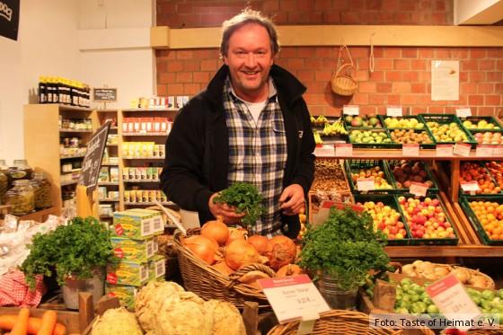 Produzent in seinem Bioladen mit Gemüse und Obst