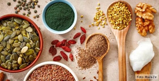 Superfoods wie Matcha und Nüsse in kleinen Schälchen