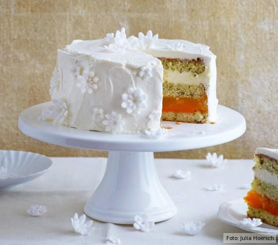 Eine angeschnittene Mango-Frischkäse-Blüten-Torte auf einer Tortenplatte.