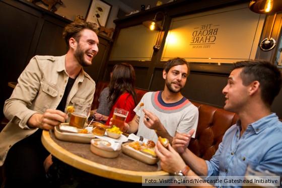 Drei Herren genießen einfaches Essen in einem Pub in Newcastle