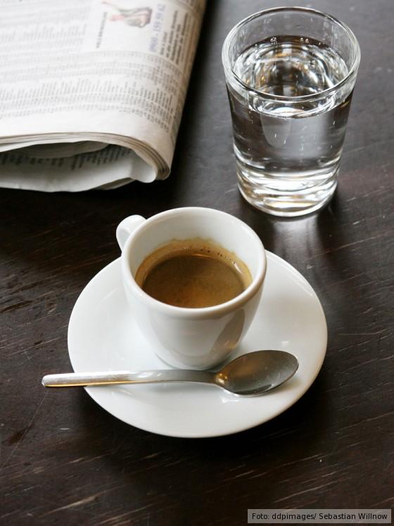 Espresso in Tasse mit einem Glas Wasser und einer Zeitung auf einem braunen Tisch