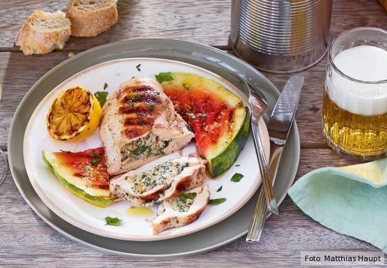 Frisch gegrillte, gefüllte Hähnchenbrust mit Wassermelone auf einem weißen Teller.