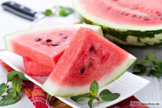 Eine aufgeschnittene Wassermelone auf einem weißen Teller, dekoriert mit Minze.