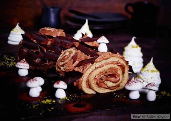 Bûche de Noël verziert mit kleinen Pilzen und Tannen aus Baiser