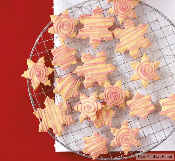 Weihanchtsplätzchen mit rosa Glasur auf einem Kuchengitter.